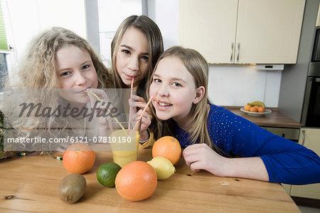 Girls in kitchen drinking fruit smoothie