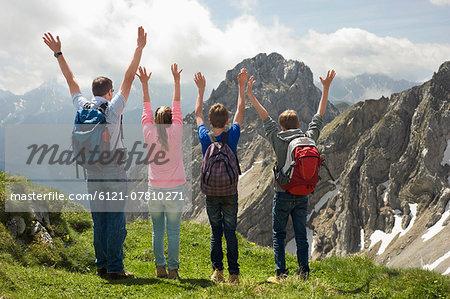 Father teenage kids standing summit Alps