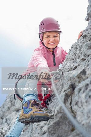 Teenage girl climbing attaching carabiner to rope