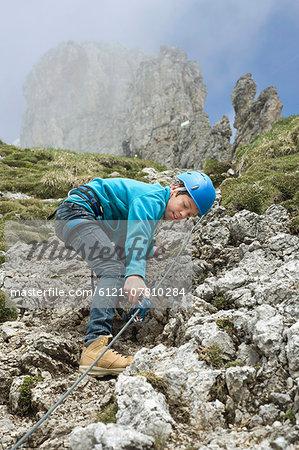 Young teenage boy climbing in mountains