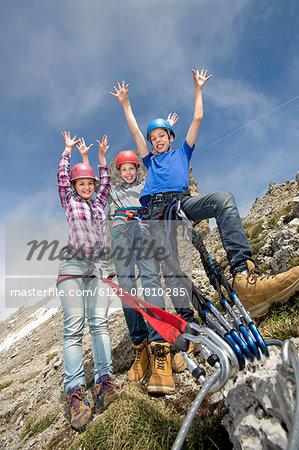 Three young teenagers mountain climbing