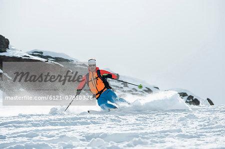 Man skiing downhill powder snow Alps