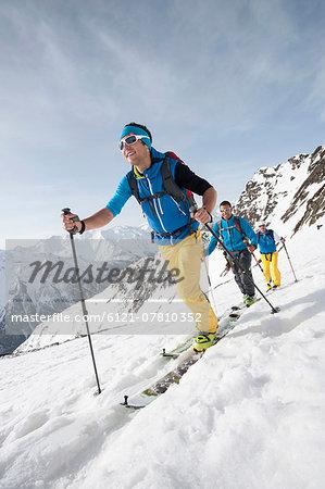 Three men skiing winter Alps cross-country