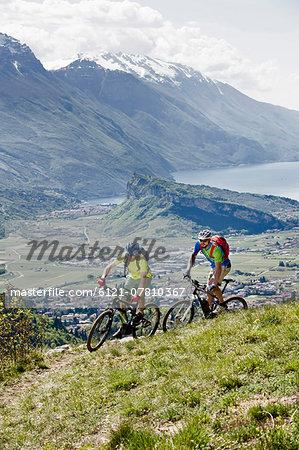 Men racing electic-mountainbikes cliff valley