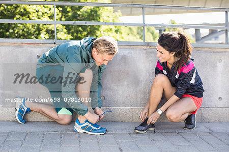 Smiling fit couple tying shoelaces before jogging on bridge