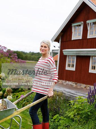 Smiling woman with wheel-barrow