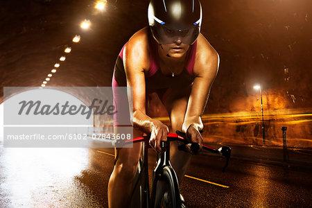 Woman cycling through tunnel