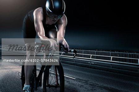 Mid adult woman cycling at night