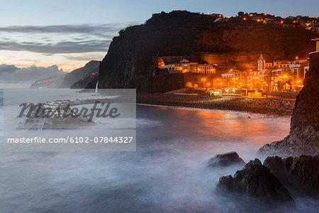 Illuminated town on rocky coast