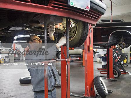 Mechanic works under auto
