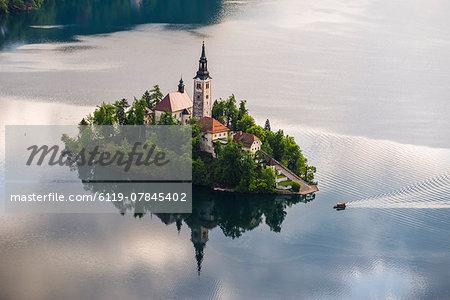 Lake Bled boat (Pletna) approaching Lake Bled Island at sunrise, Gorenjska, Slovenia, Europe