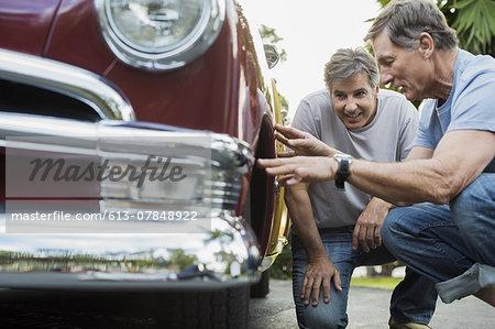 Two senior male friends examining car tire