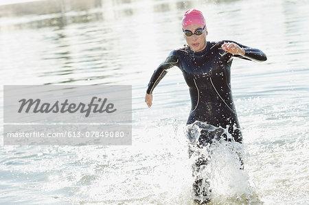 Female triathlete wearing wetsuit running in water