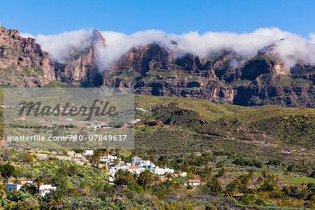 Scenic view of mountain village (San Bartolome de Tirajana) beneath the steep rock walls of the Caldera de Tirajana with a misty clouds, Gran Canaria, Las Palmas, Canary Islands
