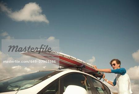Teenage boy putting surfboard on top of car