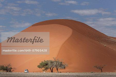 Four wheel truck parked at base of giant sand dune, Sossusvlei National Park, Namibia