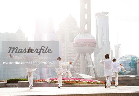 China, Shanghai. Chinese men practising Tai Chi on the Bund (MR)