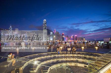 Tourists looking at Hong Kong Island skyline from Tsim Sha Tsui at dusk, Hong Kong