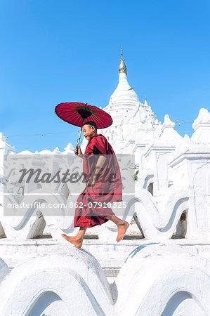 Myanmar, Mandalay division, Mingun. Novice monk with red umbrella jumping on Hsinbyume Pagoda (MR)