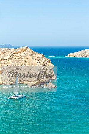 Oman, Muscat, Qantab. Rocky coastline with catamaran sailing, near Muscat