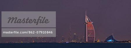 The three iconic landmarks of Subai, The 7 star Burj al Arab Hotel, The 5 star Jumeriah Beach Hotel and the Burj Khalifa containg the 5 star Armani Hotel, viewed from the Palm Jumeriah at twilight, Dubai, The United Emirates.