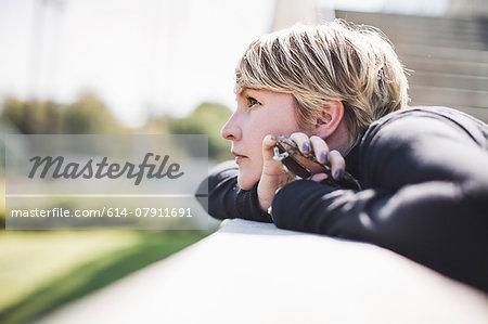 Mature woman gazing from footbridge wall holding onto smartphone