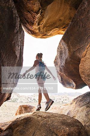 Woman balancing on rock, Joshua Tree National Park, California, US
