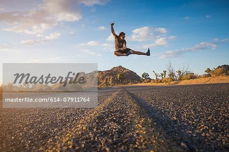 Man doing flying kick, Joshua Tree National Park, California, US
