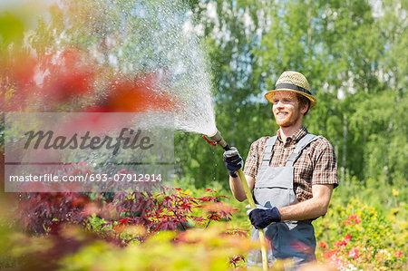 Smiling man watering plants at garden