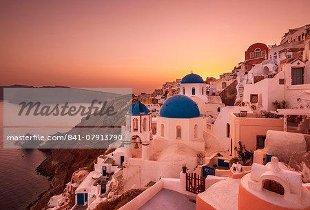 Greek church with three blue domes at sunset, Oia, Santorini (Thira), Cyclades Islands, Greek Islands, Greece, Europe