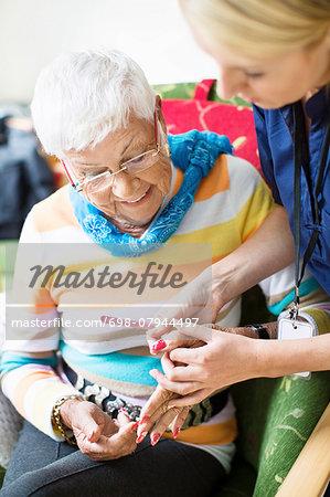 Female caretaker filing senior woman's fingernails at nursing home