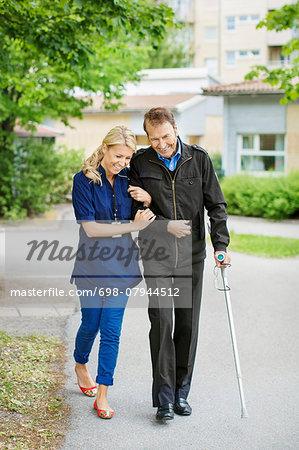 Full length of happy female caretaker walking with disabled senior man on street