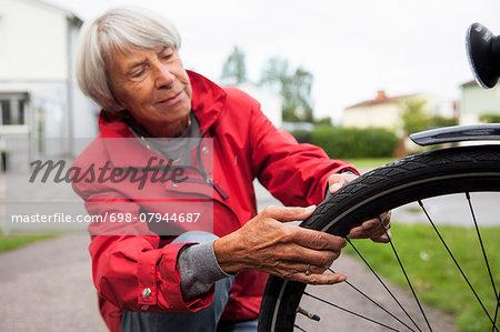 Senior woman repairing bicycle tire on street