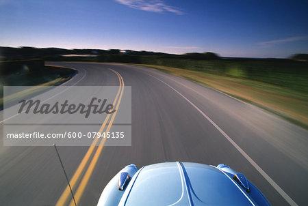 A 1974 VW Beetle drives along Ocean Avenue in Newport, Rhode Island, USA.