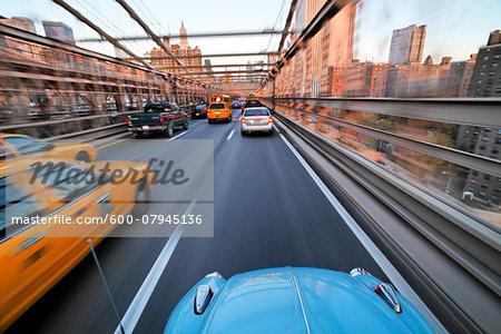 Driving over the Brooklyn Bridge in a VW Beetle towards Manhattan, New York City, New York, USA.