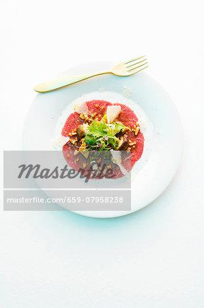 Carpaccio with a small mushroom salad and Parmesan