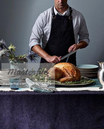 A man carving a roast turkey
