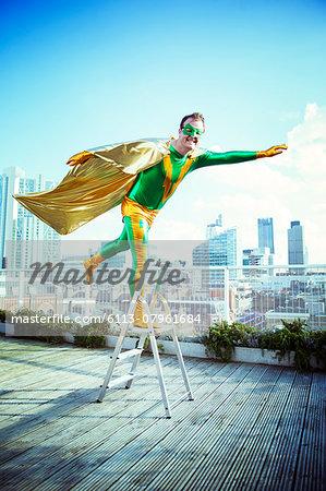 Superhero posing on stepladder on city rooftop