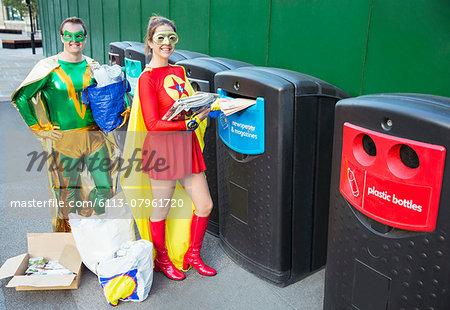 Superhero couple recycling on city sidewalk