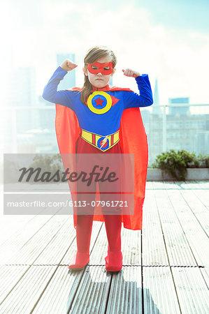 Superhero girl flexing muscles on city rooftop