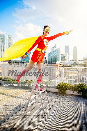 Superhero standing on stepladder on city rooftop