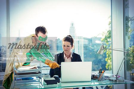 Superhero helping businesswoman working at office desk