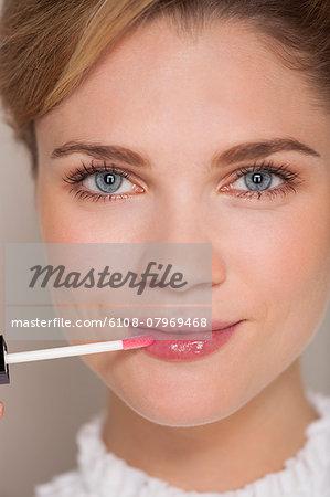 Portrait of a beautiful woman applying lip gloss
