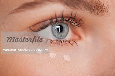 Beautiful woman applying concealer