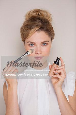 Beautiful woman applying make-up with blusher