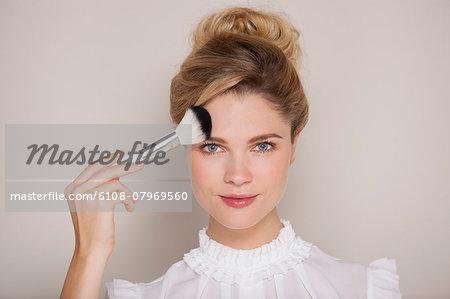 Beautiful woman applying blusher