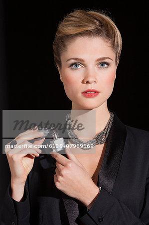 Portrait of a beautiful woman applying perfume