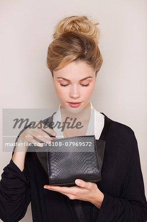 Beautiful woman checking her makeup bag