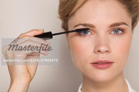 Portrait of a beautiful woman applying mascara
