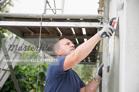 Man renovating wall outside house painting